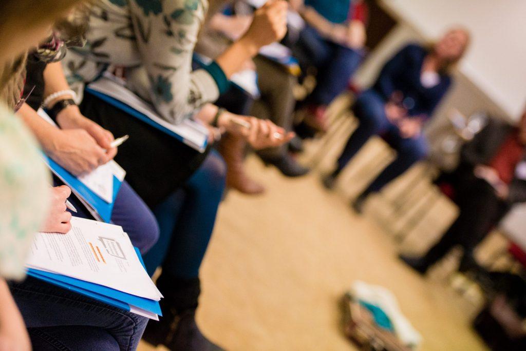 Menschen sitzen mit Stift und Arbeitsblättern zusammen in der Gruppe.