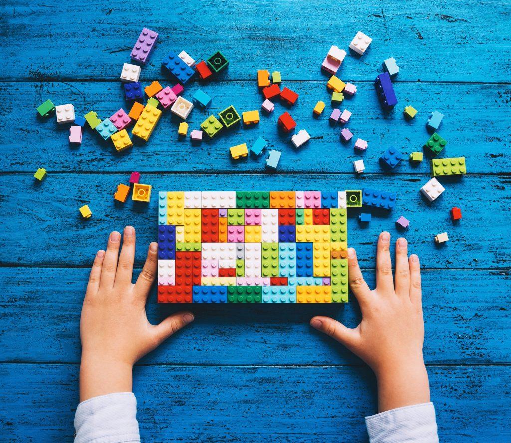 Ein paar Kinderhände, die aus vielen herumliegenden Legosteinen einen bunten Lego-Block gebaut haben.