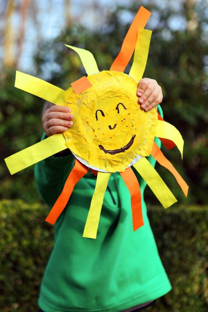 Ein kleines Kind hält eine aus Papier gebastelte, fröhlich grinsende Sonne vor sein Gesicht.