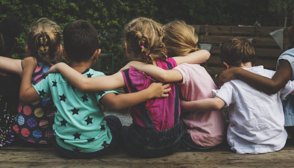 Eine Gruppe Kindergartenkinder sitzt zusammen und die Kinder umarmen sich.